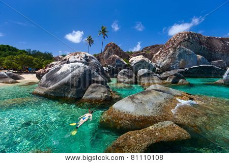 Young woman snorkeling in turquoise tropical water among huge granite boulders at The Baths beach area major tourist attraction on Virgin Gorda, British Virgin Islands, Caribbean