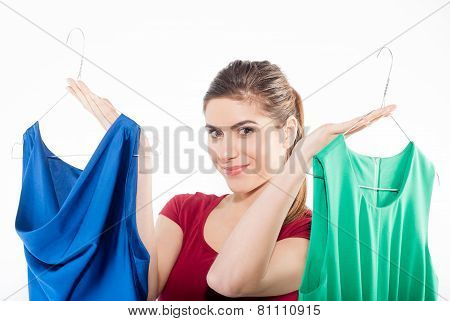Beautiful young woman with a choice of dresses which she is holding up