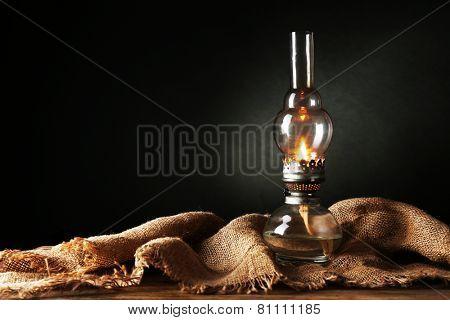 Kerosene lamp with burlap cloth on dark background