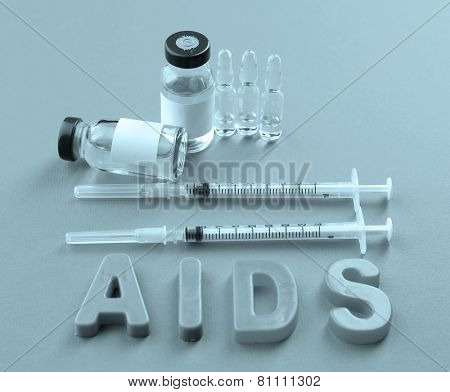 Medicines with word Aids on pink background