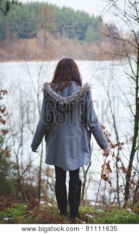 Young girl with her hair stands near the water