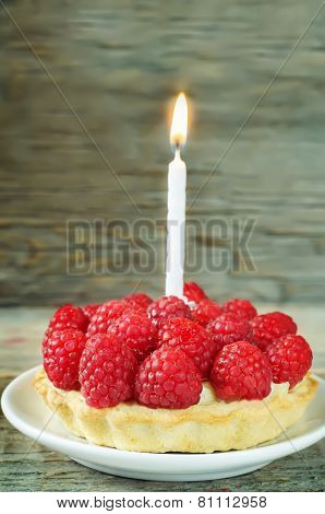Tartlet With Raspberry And Cream Cheese And A Candle
