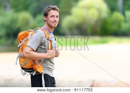 Hiking man portrait with backpack walking in nature. Caucasian man smiling happy with forest in background during summer trip in Yosemite National Park, California, USA.