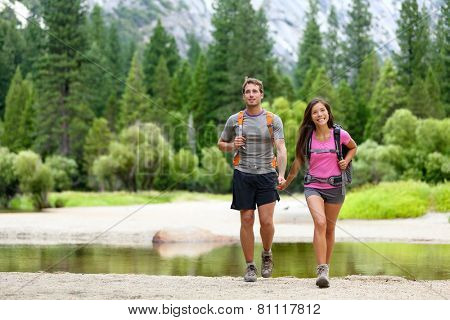 Hiking people on hike in mountains in Yosemite. Hikers young couple pointing looking up in mountain landscape in Yosemite National Park, California, USA. Multicultural couple active outdoors.