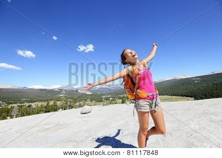 Happy hiking woman dancing in mountain landscape. Young asian adult doing funny freedom pose on top of the Pothole Dome in Yosemite National Park, California, USA.