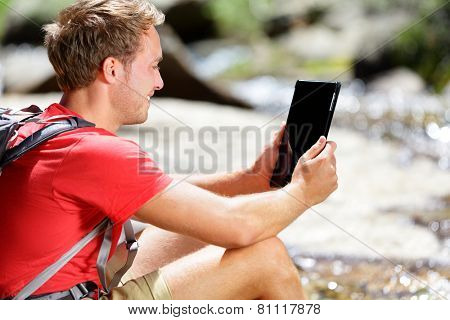 Tablet computer man hiker hiking in Yosemite, USA using travel app or map during hike, resting by river. Caucasian male hiker relaxing on a summer day.