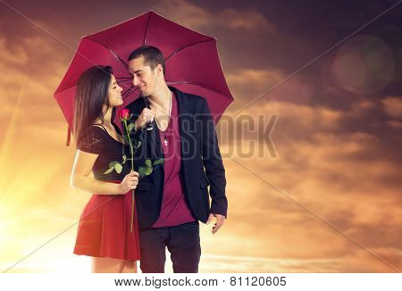 Young couple in love with red umbrella and flower over sunset sky