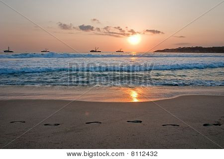 Beach Sunset With Ships And Footprintsin The Sand.