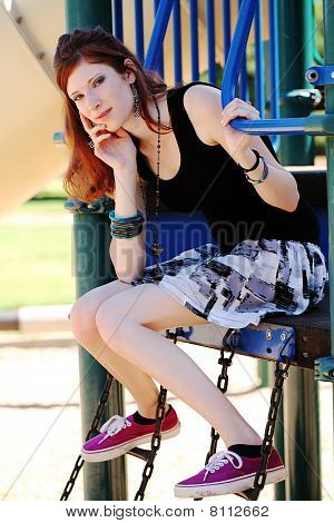 Young Teen Girl In Skirt On Playground Equipment