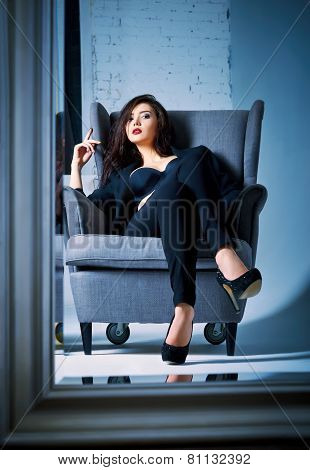 Portrait Of Beautiful Young Woman Sitting On Chair And Looking Into Mirror