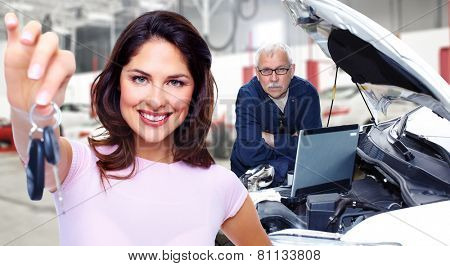 Woman holding a car key. Auto repair service