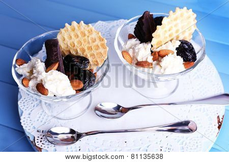 Dessert with prunes in glass bowls on color wooden table background