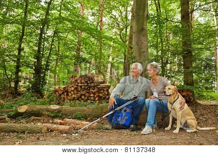 Two seniors on a hike with dog in a forest taking a break