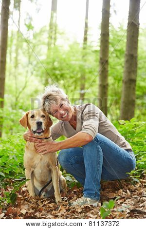 Smiling senior woman sitting with labrador retriever dog in a forest