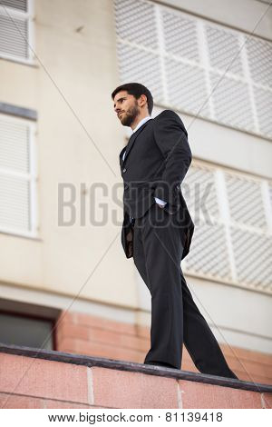 Powerful businessman walking at the roof