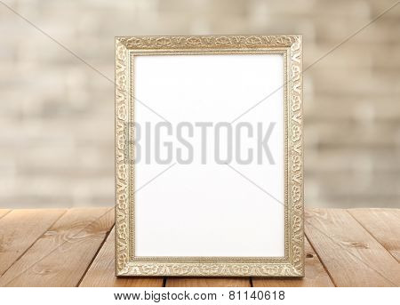 Photo frame on wooden table on wall background