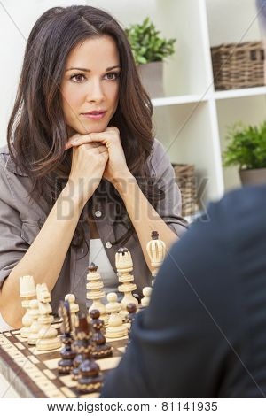 Beautiful brunette young woman playing chess game with man, boyfriend, husband