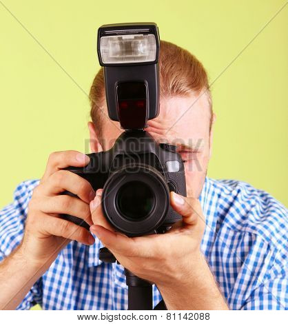 Handsome photographer with camera on monopod, on green background