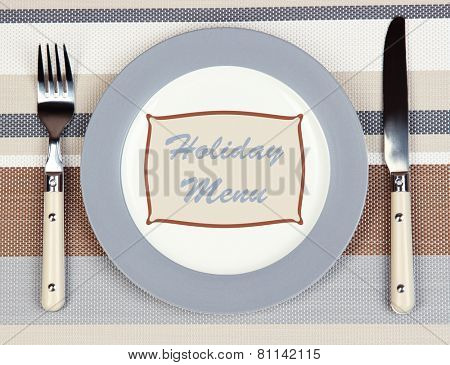 Plate with text Holiday Menu, fork and knife on tablecloth background