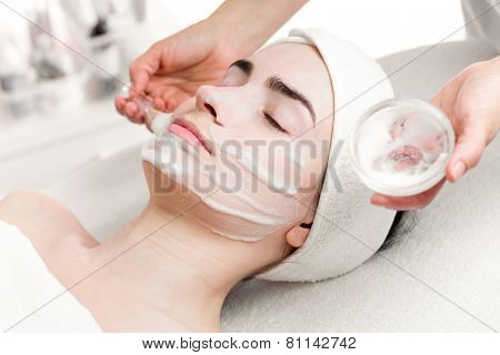 Young woman peeling foam mask applying on face