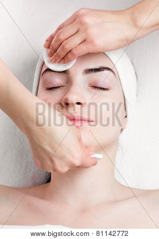 Young woman facial make up removing in beauty parlour
