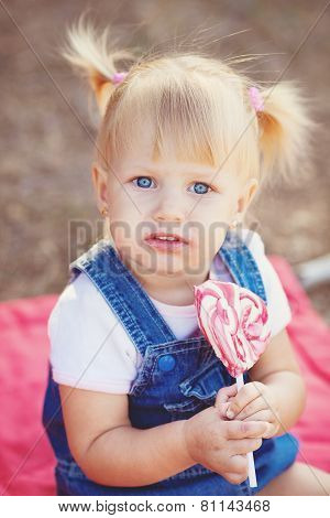 Little girl with lollipop in summer park.