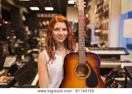 music, sale, people, musical instruments and entertainment concept - smiling female assistant or customer holding acoustic guitar at music store