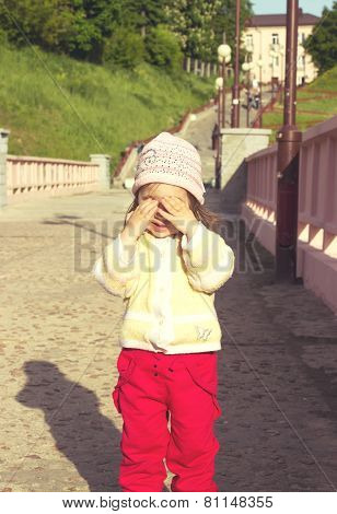 little kid is playing hide-and-seek hiding face. Toned