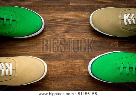 Outfit of traveler, student, teenager, young woman or guy. Colorful sneakers on wooden background.