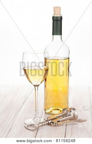 White wine glass, bottle and corkscrew on white wooden table
