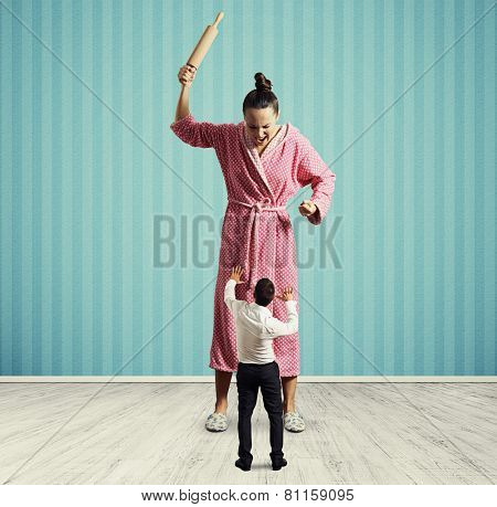 dissatisfied housewife with rolling pin screaming at small startled husband
