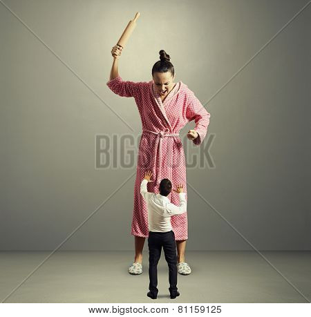aggressive housewife with rolling pin screaming at her startled husband. photo over dark background