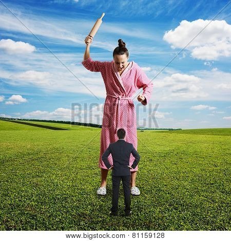 displeased woman with rolling pin yelling at small husband. photo at outdoor