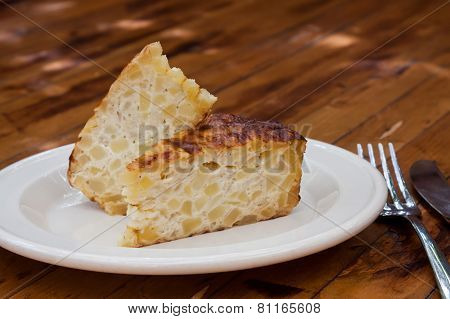 Spanish Omelet On A White Plate. The Plate On The Wooden Table. Spanish Omelette With Potatoes And O