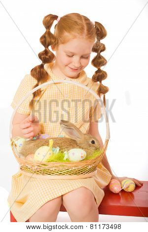 Little girl with a rabbit in  basket easter eggs
