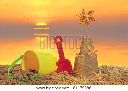Sandcastle with bucket and spade on the beach at sunset