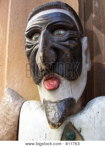 poster of Wooden sculpture of the medieval actor in masquerade mask, old city, Prague, Czech Republic