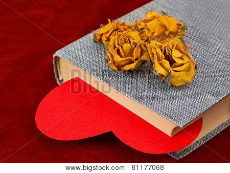 Four Dried Yellow Roses Lying On The Book With Red Heart