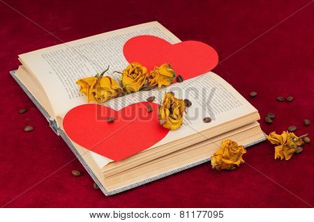 Four Roses And Two Hearts Lying On The Book With Coffee Beans