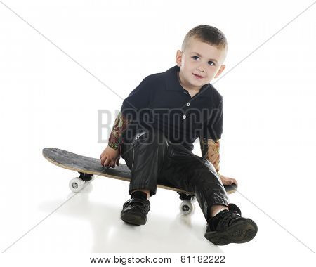 A handsome preschooler with tattooed arms and black leather pants happily sitting on a skateboard.  On a white background.
