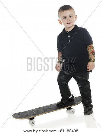 A happy preschooler standing with one foot on a skateboard with tattooed arms and dressed in black leather pants.  On a white background.