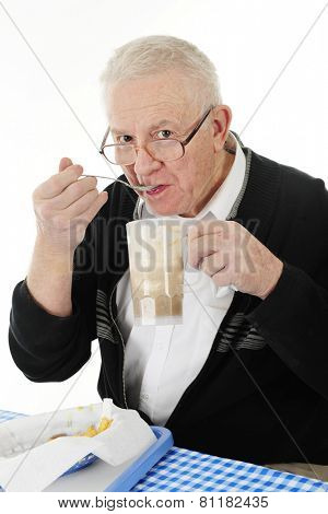 A senior adult man peering over his glasses as he eats ice cream from his root beer float.  A basket of half-eaten french fries are on the table before him.  On a white background.