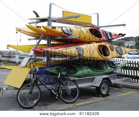 A trailer rack full of kayaks for rent in a parking lot.  A bicycle is also locked to it.