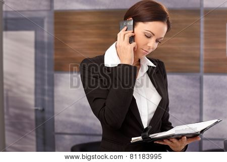 Young businesswoman talking on mobilephone, looking at personal organizer.