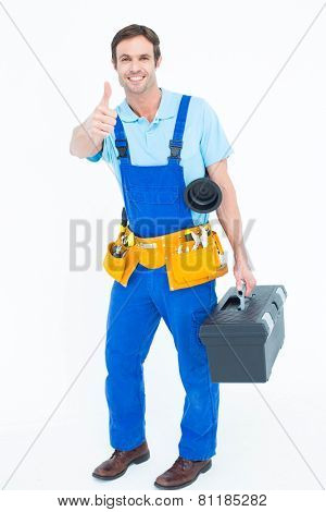 Full length portrait of happy plumber carrying tool box while gesturing thumbs up over white background