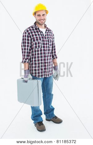 Full length portrait of happy male handyman with toolbox on white background