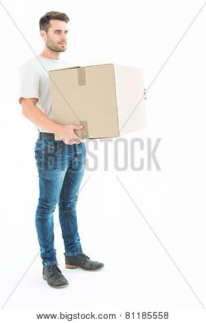 Full length of delivery man carrying cardboard box on white background