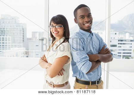 Smiling coworkers posing with arms crossed in the office