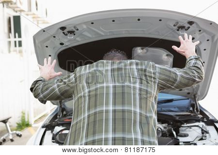 Angry man checking his car engine after breaking down in a car park
