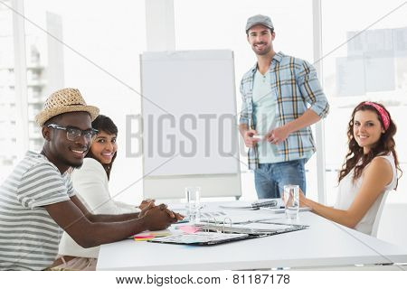 Businessman presenting and smiling colleagues listening in the office